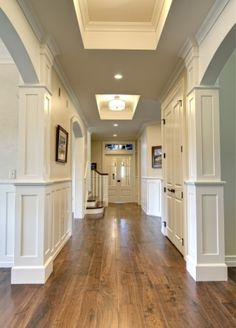 Hall/living room. Mushroom walls, white painted accents, wooden flooring.