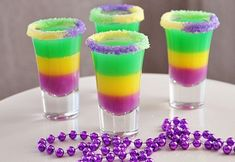 King Cake Jelly Shots -- all decorated with your typical Mardi Gras colors -- green, purple and yellow and the rim of the shot glasses are dipped in cake frosting and sprinkles that are the same color.