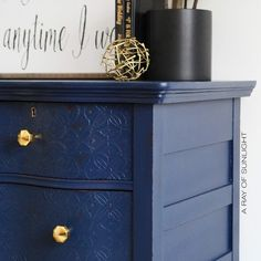 Serpentine Dresser painted in peacoat blue by Country Chic Paint with embossed drawers and gold knobs.