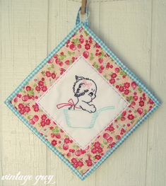 Vintage embroidery used as center of quilted pot holder
