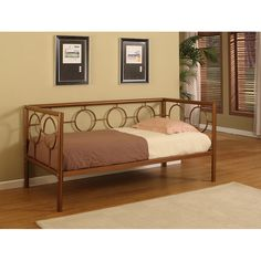 This circle design metal tubular day bed includes seven metal slats to be used as a mattress platform. Finished in a sleek coppertone color, the look will complement most decor styles.