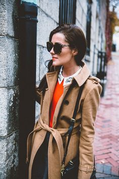 Lovely winter outfit: camel-colored coat, red sweater and decorated collar. Obviously sunglasses.