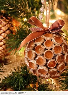 Take acorn caps dipped in glitter, attach to a ball, and top with ribbon for a festive ornament from nature. -