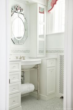 source: Design Manifest  Glamorous girl's bathroom with shaped valance in Caitlin Wilson Textiles Mint Fleur Chinoise Fabric, pale blue walls paint color, Venetian mirror, Kallista Metal Vanity Console flanked by white mirrored cabinets with marble countertops, marble basketweave tiles floor and subway tiles backsplash with mosaic ming decorative inset tiles.