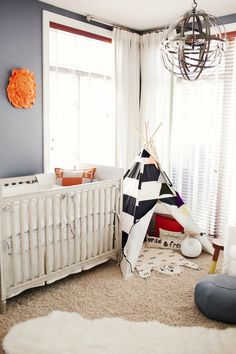 Adventurous nursery with blue and white striped teepee, orange lion face on wall, modern chandelier, and white crib