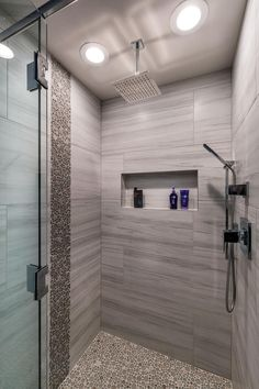 Round tiles give a pebbled look and feel to this stylish walk-in shower with a luxurious waterfall shower head.