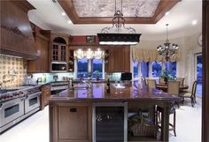 Ultra luxurious island features wine cooler and hidden storage space under large dark marble countertop in this kitchen.