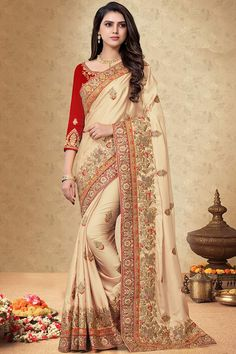 Beige silk saree with red silk blouse, embellished with dori work, resham work and sequins work. Saree with Round Neck, Quarter Sleeve. It comes with unstitch blouse, it can be stitched 32 to 58 sizes. #beige #silk #saree #blouse #Indiansaree #Andaazfashion #UK