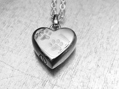 This heart locket with paw etchings is also a cremation vessel to hold the ashes of a loved one. This stainless steel pendant necklace measures