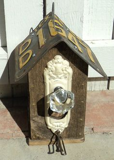Birdhouse with license plate roof and vintage door knob perch