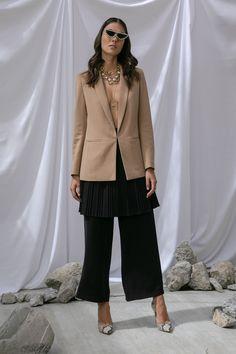 Blazer corte regular fit café y cadena con perlas MAP, falda negra plisada y pantalón negro Petite Studio, estiletos blancos de animal print Nine West, gargantilla y collar largo Aktuales.