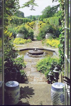 The Garden at Highgrove - The view to the west through the french windows in the hall. The design for the fountain with the millstone at its center was the combined effort of the Prince and sculptor William Pye. It stands in the middle of the Terrace Garden and draws the eye up the Thyme Walk to the distant view of the dovecote.