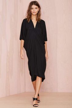 This kimono-inspired black dress features a V neckline, dolman sleeves, and a tapered fit.