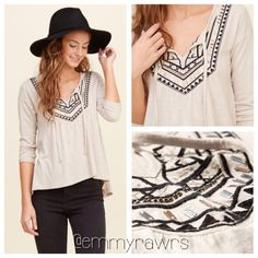 New SARAH Bohemian Embroidered Top Intricate and super soft texturing knit featuring embroidery at slit neckline with shine detailing and ties, and an asymmetrical hem. Loose fit. Perfect for the bohemian inside everyone. Tops