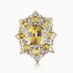 YELLOW SAPPHIRE AND DIAMOND OCTAFOIL CLUSTER CLIP BROOCH BY VAN CLEEF & ARPELS, circa 1969.