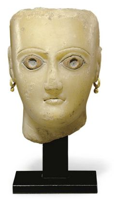 "A SOUTH ARABIAN ALABASTER FEMALE HEAD   CIRCA 1ST CENTURY B.C.-1ST CENTURY A.D.   The spade-shaped face with small fleshy lips and a triangular nose, the thin grooved brows arching over the almond-shaped eyes, the sclerae inlaid in limestone, additional inlays for the pupils now missing, the top and back of the head flat and roughly finished, the ears pierced, wearing ancient gold hoop earrings, possibly original, ""Venus""-lines along the neck"