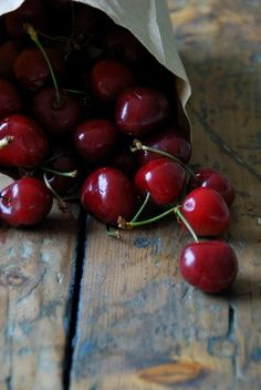 love the rustic look of cherries spilling from a bag onto a rough wooden surface ... a table, a bench, a picnic table?