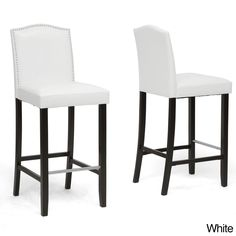 This Libra modern bar stool features solid rubber wood frame, foam cushioning, iron spring supports, and a stainless steel foot rest. Silver nailhead trim finishes this set of two handsome, faux leather stools.
