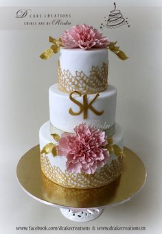 A Three Tier White Wedding Cake decorated with Pink Frill Peony and Golden Sugar Lace.
