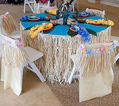 Hawaiian table set up. Towels, hula shirt cut to fit chairs, lai
