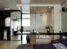 Sem paredes, o mezanino tem quarto, banheiro e closet totalmente integrados. Cabeceira preta, criado-mudo, bancada do banheiro e cuba espelhada, da Marcenaria Inovart, iluminação, da Wall Lamps, luminária Tolomeo Mini, da Artemide