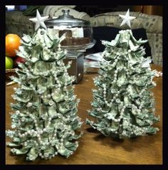 "A neat way to give the ""money"" gift and still make it seasonal. A 9"" green styrofoam cone, wire, beads and pearls for garland. Fold the money in half, then fold the halves toward each other. Use a little clear tape if needed. Run a piece of wire (with a crystal added) through the folded bill, turn down about 1"". Curl to the desired shape and start sticking them in the cone. Finish with a star on top and you're done!"