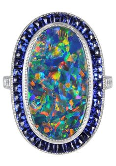Lightning Ridge Black Opal and Sapphire Ring Platinum solitaire ring consisting of one oval shape lightning ridge black opal weighing approximately 7.00 carats.