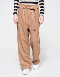 From Just Female, a modern high rise trouser in a an elegant wool blend Camel. Featuring a high rise, a 60/40 wool viscose blend, detachable belt in a matching wool fabric, with two right angle pockets at hip, a pleated structure at the waist, a welt slit