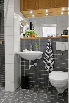 czarne i białe kwadratowe płytki na scianie w małej łazience z drewnianymi półkami i szafkami - Lovingit.pl