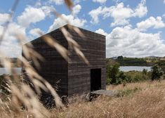 Blackened timber cabins by Cheshire Architects overlook the Tasman Sea