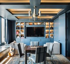 """""""Not only is blue the client's favorite color, but I derive a lot of inspiration from nature and a sense of place,"""" says Wilkinson of the soothing hue used throughout the home. """"San Francisco is famous for both its bay and its fog. Those colors are echoed in the palette."""" A circa-1910 rug from India and custom walnut-and-steel game table give a worldly feel to an office that doubles as a guest room."""