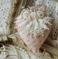 Srdíčko ve stylu Shabby chic Srdíčko je z jemné bavlněné látky, růžové barvy.Zdobení krajkami, ručně tvořenými růžičkami, obojí smetanové barvy. Doplněno perličkami a srdíčky. Řetízek pro zevěšení Barvy starorůžová a smetanová rozměr 10 x 12 cm + řetízek