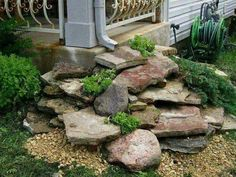 Such a creative idea! (if you have a high enough clearance under downspout) Stack flat rocks under the gutter downspout for a beautiful dry waterfall landscape idea. Love that they added ground cover plants too! Great for hiding an unsightly corner. :)
