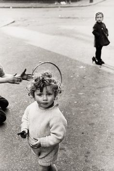 Here a young child poses with what looks like a toy gun while in the background a young gi...