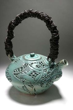 cone 10 highfired carved teapot (20 inches tall). thrown by me, carved by Diane KW.  handmade handle by me !  ALSO ! if you are in Honolulu on Nov. 25 2008  at 5PM-8PM  please come to our Linekona Art Center Ceramic Exhibition & sale for our opening. percentage of proceeds go to the art center.  strobist info.  vivitar 283 baretube modified armatar in a large 22inch beauty reflector above, tilted slightly towards camera. 1/200 at f/5.6 iso 200.   i just redid the handle. so i'll reshoot it…