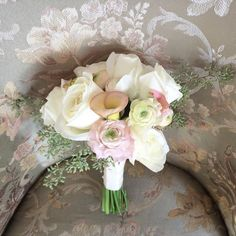 Bridal bouquet with white roses, pale pink ranunculus, calla lilies and eucalyptus seeds