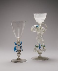 Drinking-glass; very thin and light; stem in form of hunchback dressed in trunk hose, figure blown into a mould and hollow, but not communicating internally with the bowl; stands upon two scrolls; details in blue, white and green glass, with gilding. Italy (Venice), 16th century.