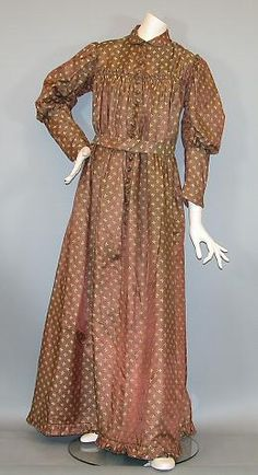 """The dress, of printed brown silk with a small tan leaf pattern, is in a """"Mother Hubbard"""" style, long sleeves, small rounded collalr, high yoke accented with a small ruffle from the gather skirt fasten to the yoke, buttoning down the front (16 domed brown buttons - all present - into 16 handmade button holes), long leg-o-mutton sleeves, small box pleated flounce at hem. There is a small half belt (built into the dress) that fastens in the front (at the natural waist, while in the back there…"""