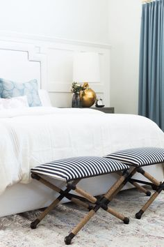 Small collapsible chairs at end of white bed
