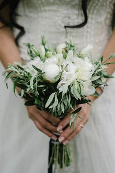 Bouquet for sicilian wedding made of white eustomas, white peonies and branches of olive trees