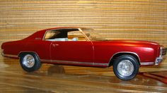 "This model is a 1970 Chevy Monte Carlo. It has spark plug wires, after market wheels and tires.  The car has metallic maroon paint which has been polished to almost mirror finish.  The interior is off white.  The license plate is 1970 Indiana.  There is a little discoloration over the top left of the grille and a paint chip above the right headlight.  The car is 8"" x 3"" x 2 1/4"".  It comes in its own plastic showcase."