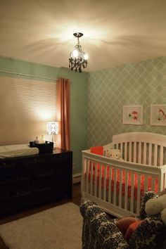 white crib with black dresser and light green walls