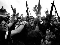 """1974 Carnation Revolution - Crowds in Lisbon join in with revolutionary soldiers after the overthrow of Fascist """"Estado Novo"""" regime, inserting carnation flowers into the muzzles of the soldiers rifles."""