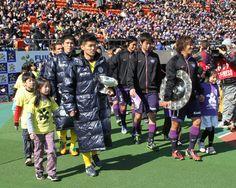 [ FUJI XEROX SUPER CUP:広島 vs 柏 ] ついに選手入場。両チームのキャプテンがそれぞれの王者の証、J1リーグ優勝シャーレと天皇杯を抱えピッチに向かう。  ★「FUJI XEROX SUPER CUP 2013特集」グルメ&ゆるキャラ&もちろん真剣勝負も!  2013年2月23日(土):国立競技場