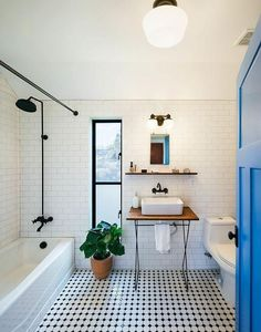Gorgeous white floor to ceiling tiled bathroom with black and white patterned penny tile flooring, black show fixtures and a bright cobalt blue door.