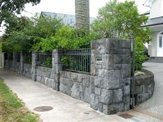 Honeycomb basalt entrance pillars and boundary walls with integrated sliding gate