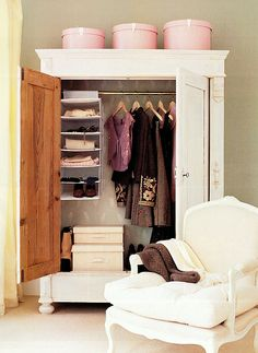 White armoire with wallpapered interior and pink hat boxes