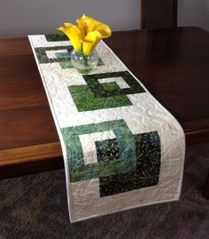 Modern Batik Table Runner, Handmade Green Quilted Tablerunner, Green and Cream Wall-hanging, Reversible Table Quilt, Contemporary Dining Room Decor ----------------------------------------- Although designed as a modern look table runner, this quilt could also be used to adorn your wall, a dresser, coffee table, sofa table, buffet, desk, bed or piano top. The green and cream color scheme is versatile and can be used in any season. A layer of batting enclosed between two layers of cotton…