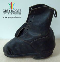 Custom made for George Dierlamn who had a crippled foot, this shoe is made of black leather and is double stiched in white. The distored shape allowed for the man's foot. The boot is lined in black and white-striped cotton. Grey Roots Museum & Archives Collection.