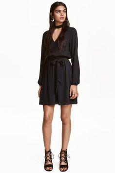 Robe courte: Robe tissée courte. Modèle avec petit col droit et partie découpée devant et dans le dos. Boutonnage sur la nuque. Manches longues. Découpe élastique soulignée d'une fine ceinture amovible à la taille. Doublée.